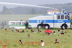 Protesters and water cannon in a field